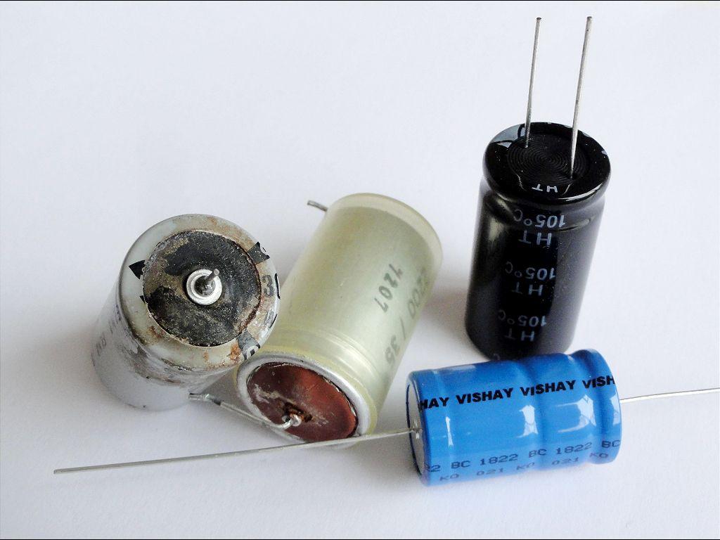 Links op de foto: Electrolyt lekkende en bijna ontplofte condensatoren, Rechts op de foto: de nieuwe vervangers